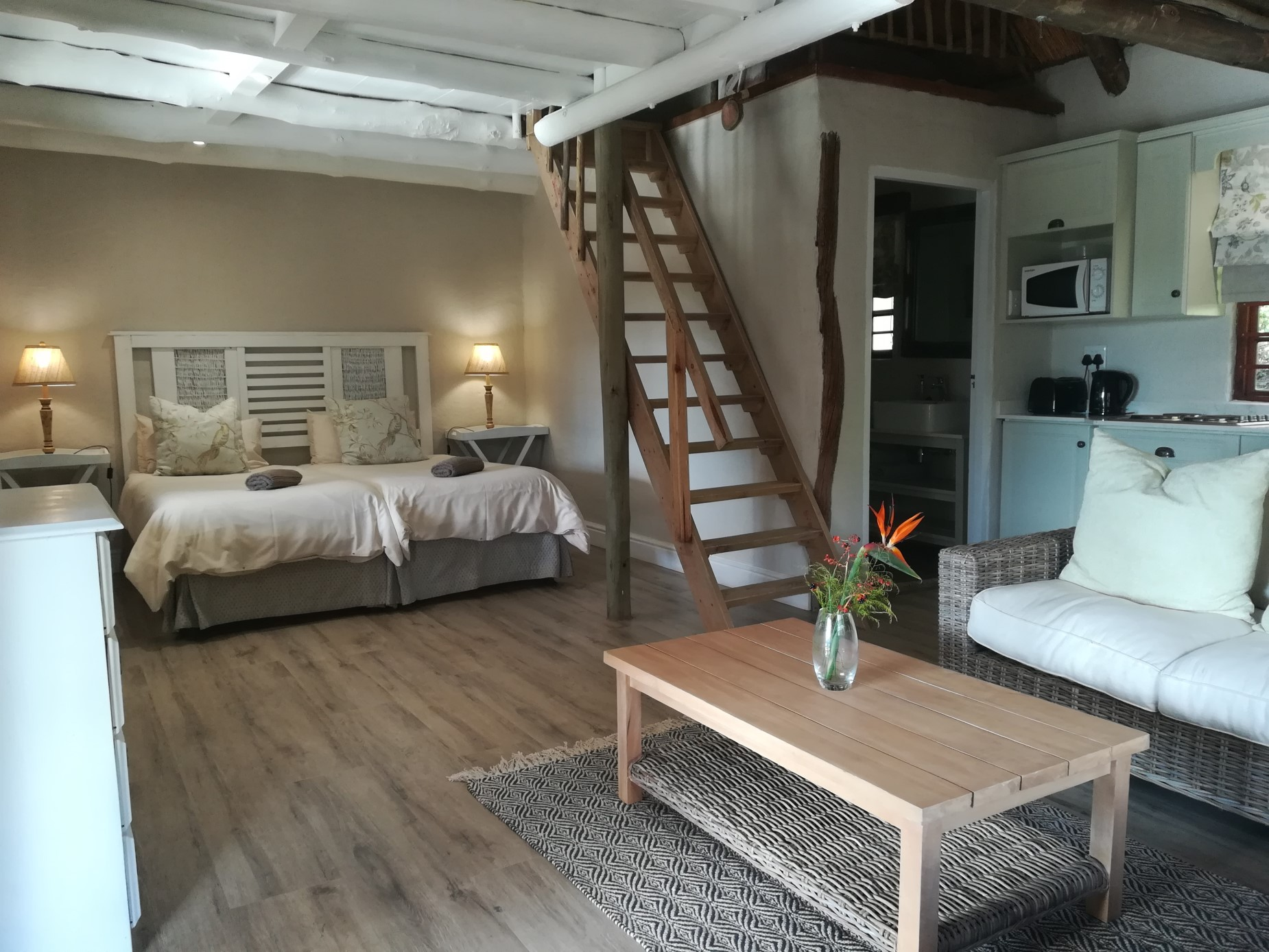 Bedroom with stairs leading to upstairs loft bedroom